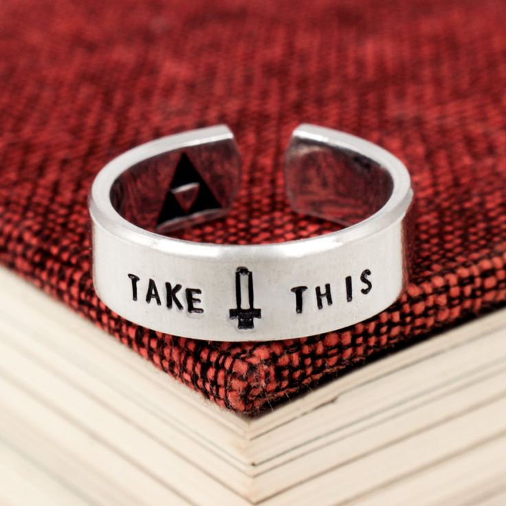 "This ""Take This"" aluminum ring is stamped by hand and has a cool little Pixel Sword right in the center. This ring is made on a 1/4"" wide aluminum blank and hand wrapped to fit your size. Please avoid"