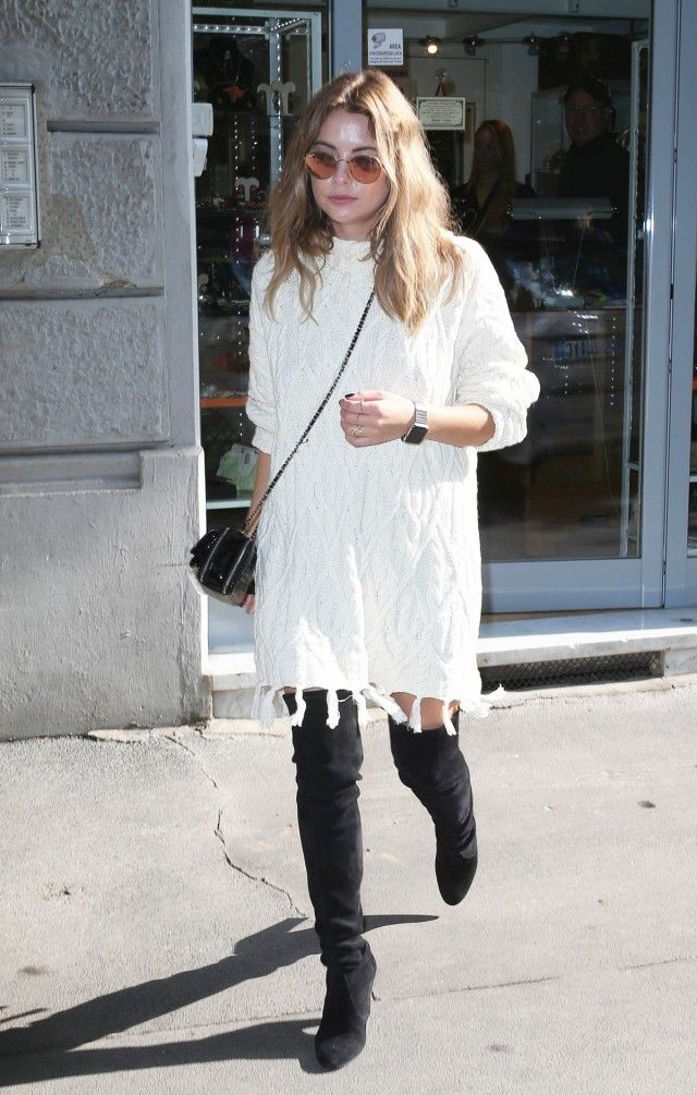 Ashley Benson wears a cable knit sweater dress with thigh-high boots and round sunglasses