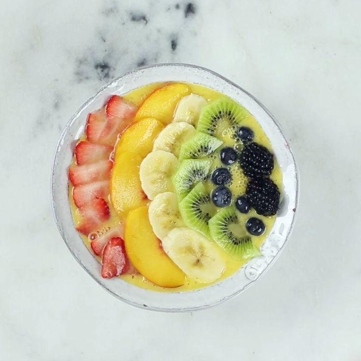 A colorful smoothie bowl using mango and fresh fruit.