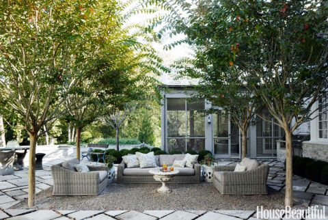 """A gravel courtyard on the back terrace defines the outdoor living room. Crape myrtles form a """"ceiling"""" over the furniture: a Provence sofa and chairs from Restoration Hardware, an antique garden urn transformed into a coffee table, and vintage ceramic garden stools. """"It's such a sheltered area, birds like to nest in the trees,"""" Whitson says. """"Sometimes it feels like you're in an aviary."""" The terrace pavers are reclaimed limestone from English sidewalks."""