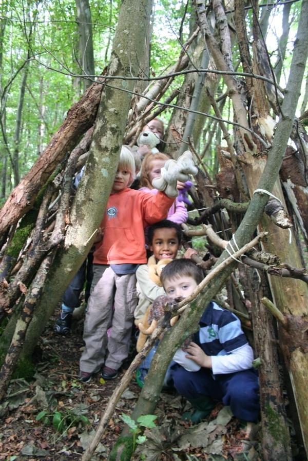 Children in twig structure in UK Forest School.