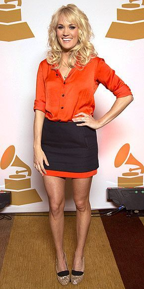 Since she no longer has her official purse holder, the star's solution is to leave her bag behind and opt for impactful shoes instead – which she wears with a black-and-tangerine number and choppy new bangs at a Grammy Nominee party in Nashville.