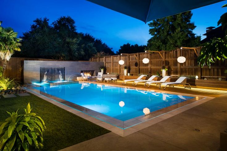 This unique back yard brings in a variety of design elements which all come together to create a fun and unconventional space. The sleek style of the modern stone wall is continued around the pool with modern furnishings and LED lighting. A more traditional fence gets some quirk with funky hanging light fixtures, and a fire pit and water feature give the yard a more luxurious feel.