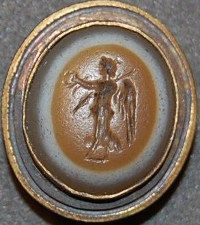 Convex sardonyx gem engraved with a draped Victory holding a wreath and a palm-branch (?).
