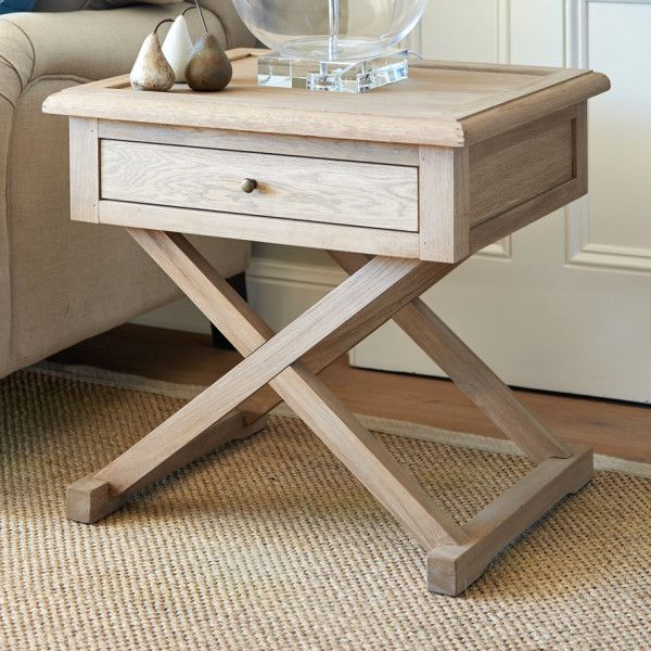 Our Hamptons style oak side table features cross legs and a small drawer for handy storage. Perfect as a side table to a sofa or as a bedside table.