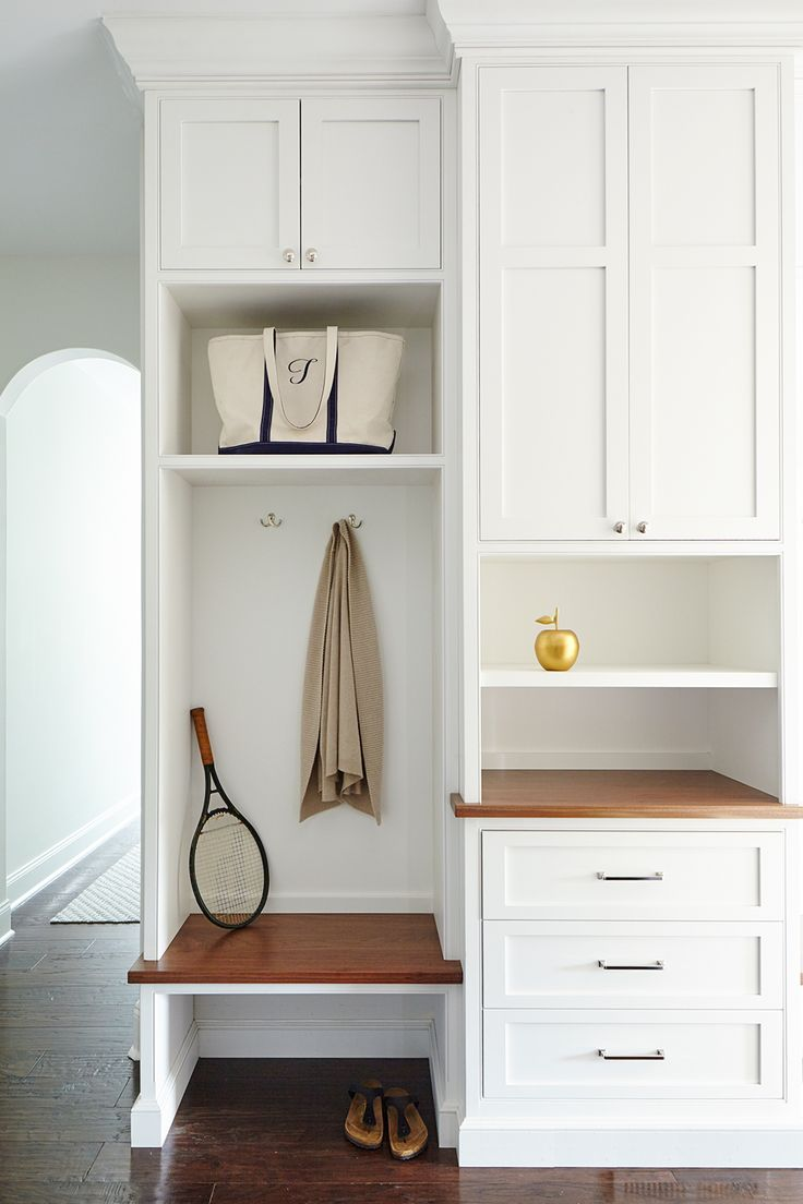 Custom Designed Mudroom Built-ins with Polished Nickel Hardware, and walnut accent. Designed by SHOPHOUSE Interior Designers. White Built-in with Crown molding with cubbies for the whole family. www.shophousedesign.com