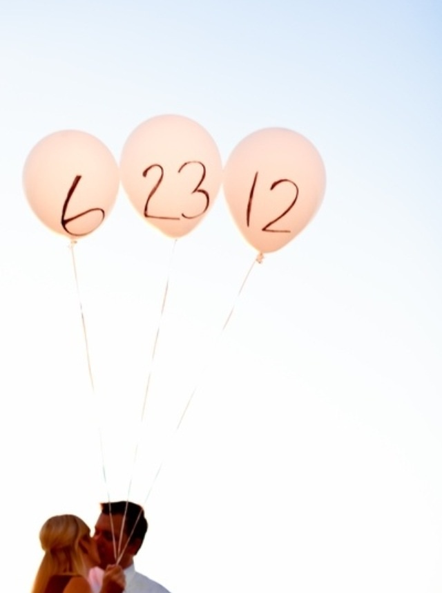 Cute wedding picture. They hold three balloons with the wedding date written on them