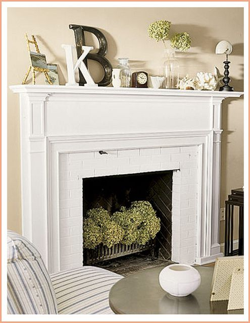 White brick fireplace with hydrangeas.