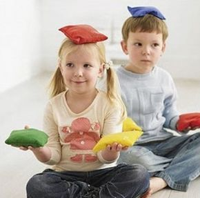Gymles kleuters met pittenzakken 5 - Laat de kinderen de pittenzak op de grond leggen verspreid door het speellokaal, en geef opdrachten als 'spring over de pittenzak', 'ga op de pittenzak staan', 'loop om de pittenzak heen'.