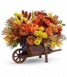 una carreta cafe con flores frescas, uvas y calabazas artificiales para dale un toque unico a tu oficina o a cualquier habitacion de tu casa.