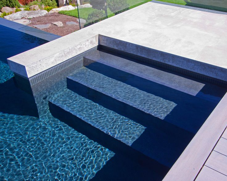 ALKA POOL - A combination of the rich custom blended charcoal colored plaster with the Smoke Grey glass tile band creates a striking contrast against the cool tones of the patio and enhanced with the infinity edge.