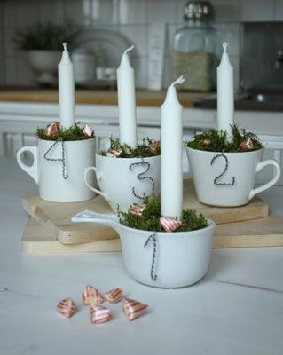 Advent Calendar: Coffee cups stuffed with moss to hold white candles. Wire numbers are hooked onto each cup. Use red & white mints to decorate the moss. Each evening of advent, there is one more candle to light, & by Christmas Eve you should have a room full of glowing light!