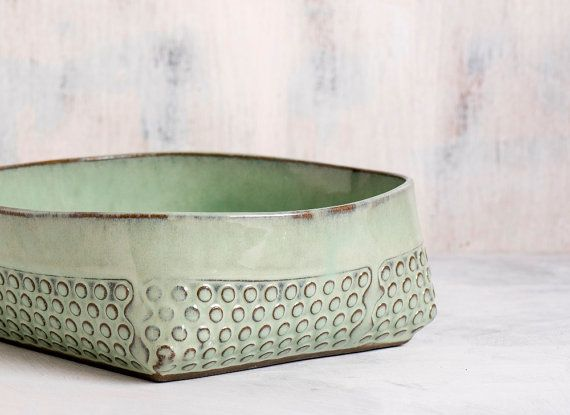 Mint green stoneware salad bowl, made of light green matte glazed ceramic with a light Relief polka dots pattern. Bowl is folded from a ceramic surface by hand creating square corners. Great to serve your fresh picked fruits or a green salad. could be easily used for cooking or baking a special dish at the oven, and straight to the table for a unique flavor and look. Each piece is made by hand, using folded stoneware sheets stamped with polka dot pattern. Dipped in light green matte glaze…