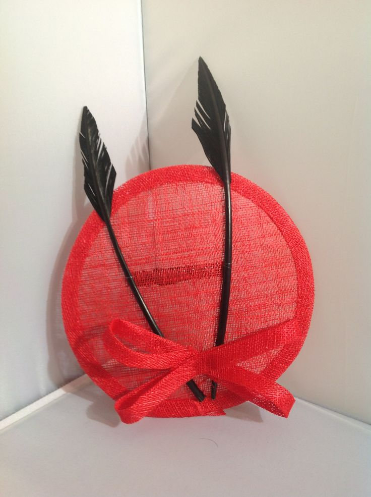 The Kelly is a large fascinator on a comb the large ruby red base is sinamay with a centre piece of a ruby red sinamay bow with large onyx black arrow feathers to finish. $80 AUD.