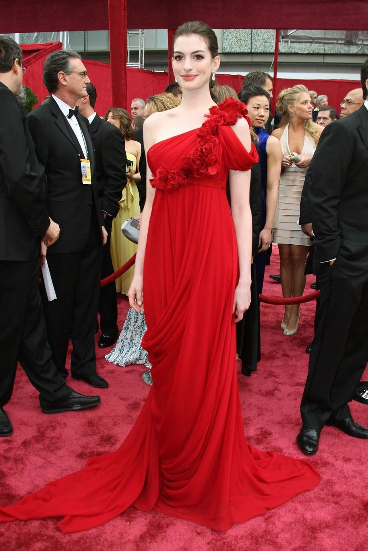 Anne HathawayinMarchesa: In 2008, the actress took to the red carpet in this floor-length crimson gown with intricately made flowers leading from her shoulder to the waist. The dress complimented the star's porcelain skin tone perfectly – and she kept her accessories minimal to keep the focus on the Marchesa gown.