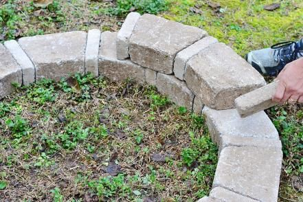 The first tier of your fire pit is the most important.  Create your first tier by forming a circle, alternating the large and mini bricks to create a pattern.  Using your level, make sure the bricks are relatively even all of the way around.  If the circle is more than an inch or two uneven, remove the higher bricks and dig out the dirt underneath them until they are level with the other side.  This is an important step to insure your fire pit is level before building the additional tiers.