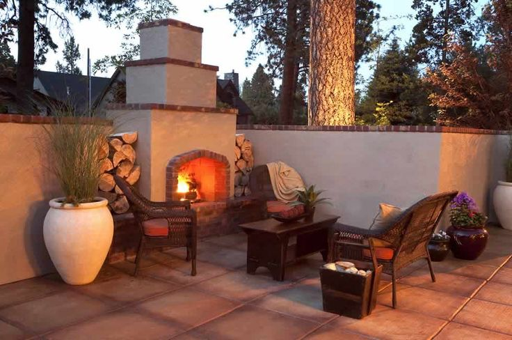 Stucco and brick outdoor fireplace for patio, and matching retaining wall out near pool deck near fencing