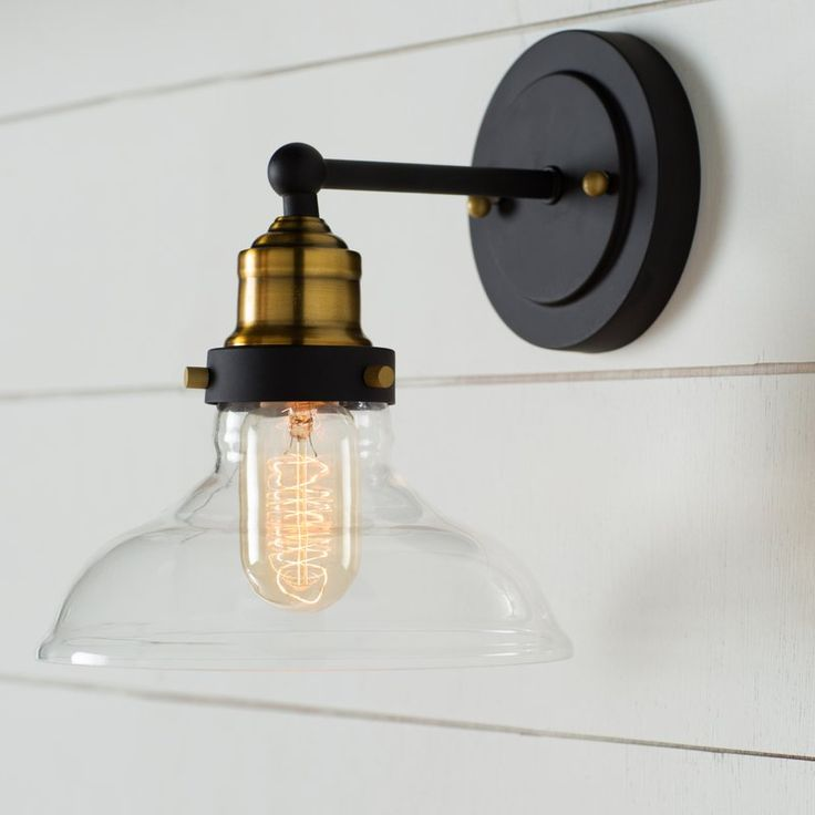 Factory-chic flair meets upscale charm with this eye-catching wall sconce, featuring a clear glass shade and an oil-rubbed bronze finish. Set two over a clean-lined wood console table in your living room to put a spotlight on au courant curios and stacked art books, then set a long wall mirror between the pair to round out your aesthetic in simple style. For an ambient touch in your dining room, try nixing the chandelier and arranging a row of these luminaries on a bare wall instead, then…