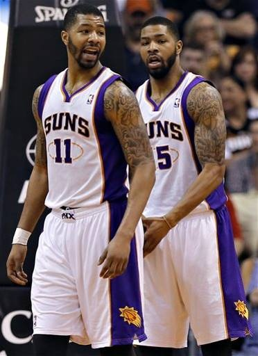 Phoenix Suns' Markieff Morris, right, and his twin brother, Marcus Morris (11) wait for play to start against the Houston Rockets'  during the second half of an NBA basketball game, Monday, April 15, 2013, in Phoenix