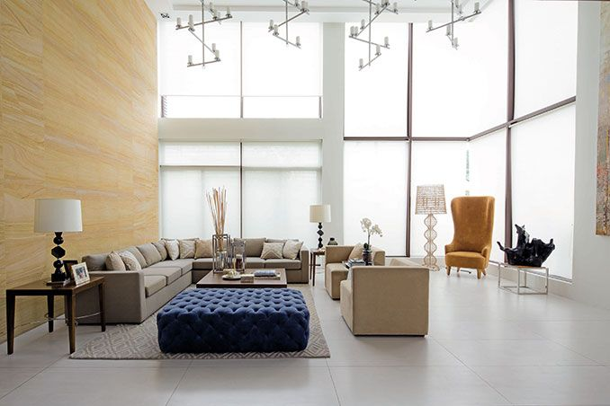 The living area is furnished with a sectional sofa, a pair of armchairs, and a tufted ottoman upholstered with a royal blue fabric. Although the homeowner initially wanted a crystal chandelier, the interior designer thought that it would not fit the theme of this modern tropical house. With this in mind, she chose lighting fixtures with cascading candleholders.