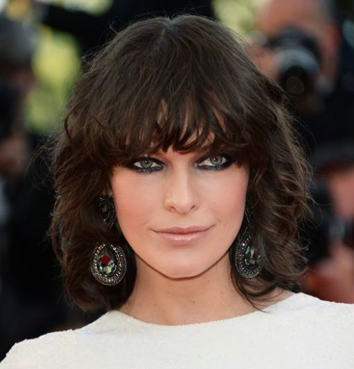 dark shoulder length hair with bangs & dark lined eyes on Milla. the look is sophisticated yet sexy.