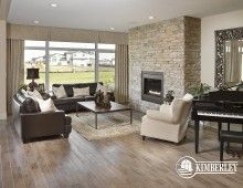 Great room with stone feature wall around the gas fireplace, piano, expansive windows. Our 2014 Cash & Cars for Cancer Lottery Home| The Legacy model by Kimberley Homes  #interiordesign #newhomedesign #homedesign #newhome #customhome #yegre #buildwithkimberley #kimberleyhomes #fireplace #greatroom #livingroom #bonusroom #stonewall #accentwall