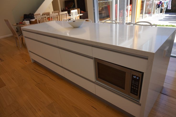 Island cabinetry with built in microwave Stone bench top with waterfall ends