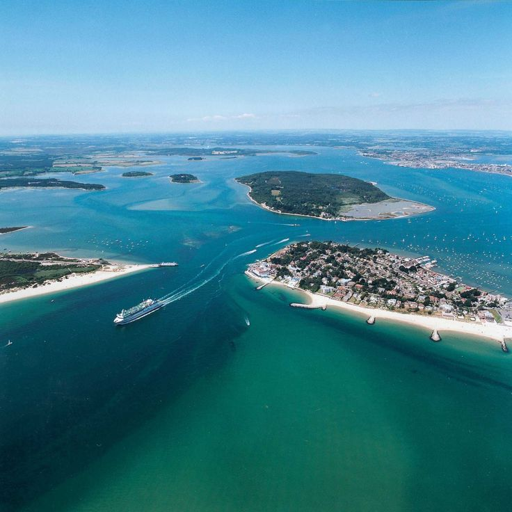 Poole harbour. Here you can see the chain ferry at the harbour entrance linking Sandbanks with Shell Beach. The island in the middle is Brownsea Island, the home of scouting.  Poole town is in the distance in the top right corner and Dancemania is just out of shot.