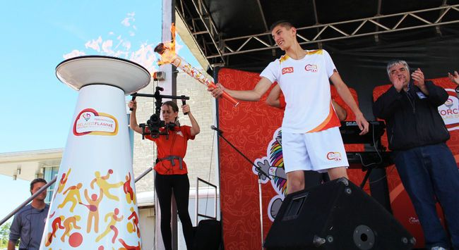 Pan Am Games Torch Relay torchbearer Teodor Mlynczyk lights the cauldron on stage during the Community Celebration in Bradford, Ont. on Friday June 26, 2015. Miriam King/Bradford Times/Postmedia Network