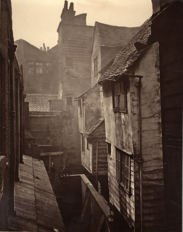In Cloth Fair, next to Smithfield Market  1882. This is amazing. Movie sets and carefully staged era photographs seldom communicate how dirty things had to be in cities back then. The smoke and dung and coal everywhere...the crooked houses, how cramped it all had to be. These pictures are fuel for my mind whenever I read historic fiction. It wasn't Jane Austin movies. It was this.