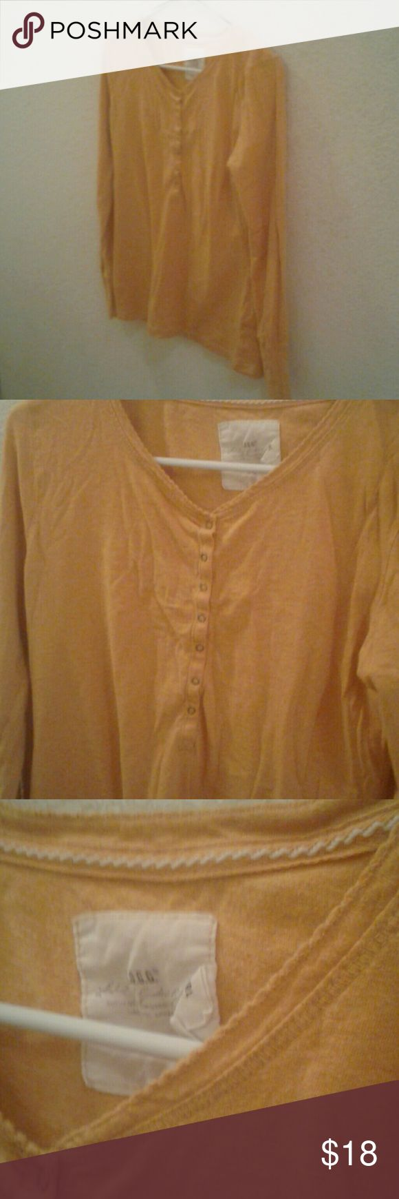A orangish yellowish long sleeve tee Has buttons and folding sleeves, is cute and comfy, goes with anything, is basically the bomb. Com h and m Tops Tees - Long Sleeve