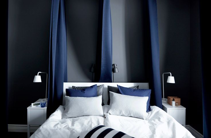 Padded, dark blue curtains hung around the outside and in between the bed help block out sound and light. Dark walls and crisp white sheets help create a feeling of calm.