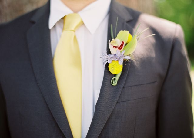 Yellow finesse roses, green cymbidium orchids, yellow billy balls, hot pink peony, blue aggies, orange gerbers and orange ranunculus were used to create this colorful bridal bouquet!!  The grooms bout was perfectly bright as well. We used a mini green cymbidium, blue aggies, and a yellow billy ball for his design.