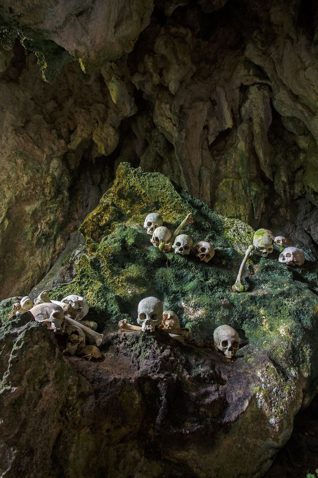 In Sulawesi, Indonesia, in an area known as Tana Toraja, people bury their family members in naturally formed caves. They believe their deceased loved ones live on in these caves, which serve as family crypts.