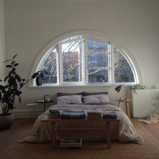 This fabulous arched window is the perfect headboard in this bedroom.