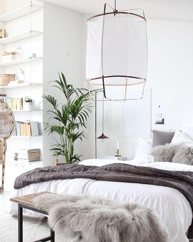 Mysigt sovrum med bänk framför säng och bokhylla från golv till tak.