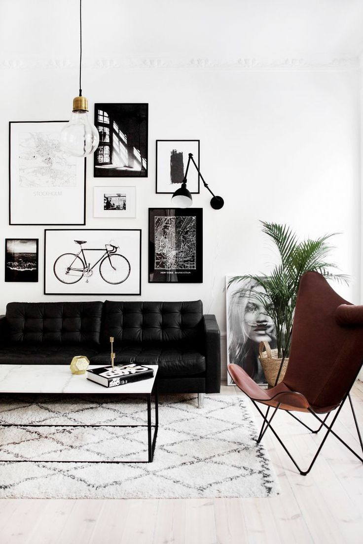 Leather butterfly chair is always one of my favorite. Love minimalistic brass pendant light here, black sofa and gallery wall. Moroccan rug and industrial coffee table compliment the look.
