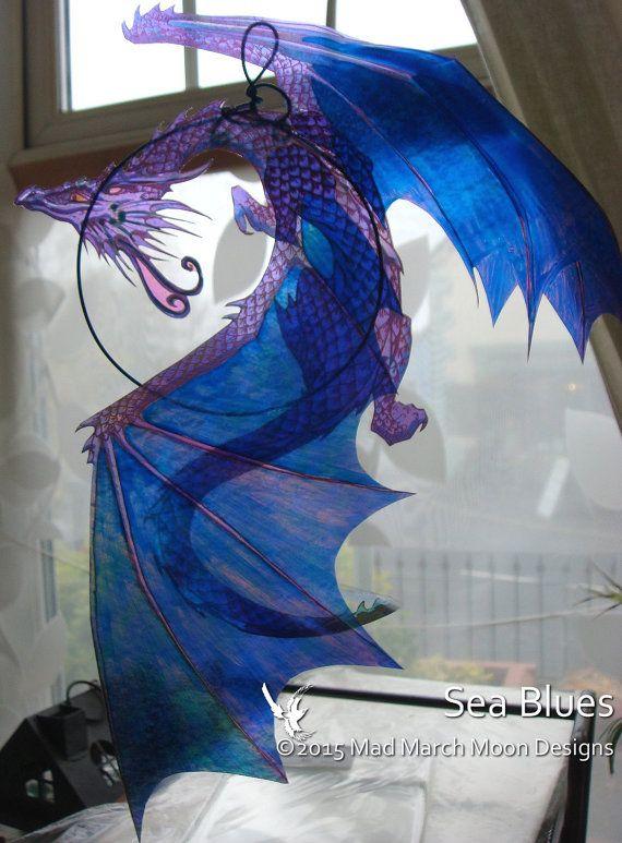 Dragon Suncatcher, 3D iriserende transparante raamdecoratie beschikbaar in 8 verschillende kleuren.  Gemaakt uit meerdere lagen van acetaat en regenboogkleuren deze draak in een gekleurde draad ring zweeft (kleur kan variëren), vangen en weerspiegelt licht en een beetje van dazzle toevoegen aan uw huis. Met de gevouwen transparante vleugels diepte en belang toe te voegen de draken staart gratis loopt vast in een spiraal verzenden buiten glinsterende flitsen van zacht licht gekleurd.  Een…