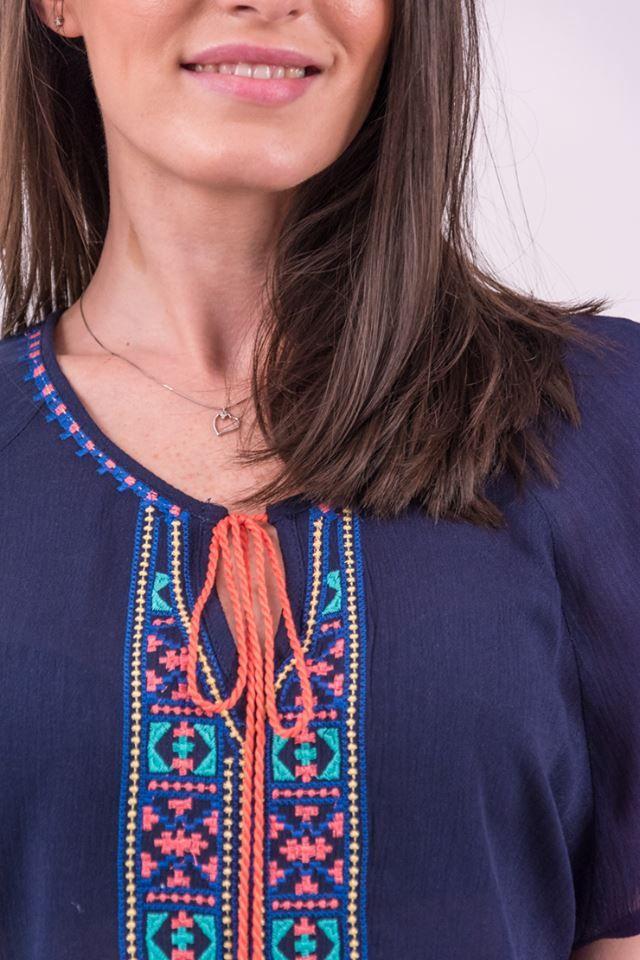 Bluză din material texturat fin, vaporos, de culoare albastră cu decolteu caftan. Este acccesorizată în partea frontală,cu broderie decorativă, multicoloră dispusă vertical. Prindere cu șnur cu canaf de culoare roz. Mâneci scurte, neaccesorizate. Terminație simetrică, rotunjită.