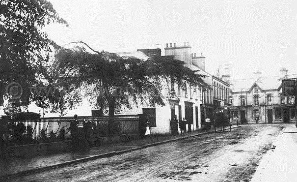 Pic of Lower Main Street, Ballyclare in 1910. The railings surround Ollar Lodge and the Private School was held in this building, entrance was made by an entry beside the shop where the group of people can be seen.