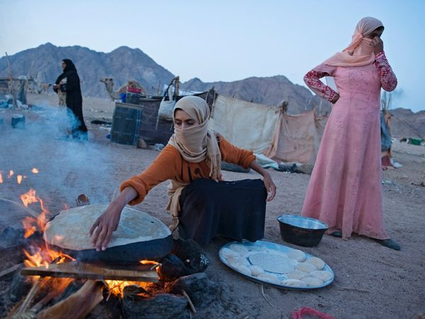 Bedouin Camp, Egypt  Photograph by Matt Moyer, National Geographic  Simple bread called feteer helps feed Bedouin families in a squatters' camp near Naama Bay at the southern tip of Egypt's Sinai Peninsula. Drought has pushed tribes down from the mountains to seek work, but many Bedouin men remain jobless in a country that has never embraced desert-dwelling tribes.