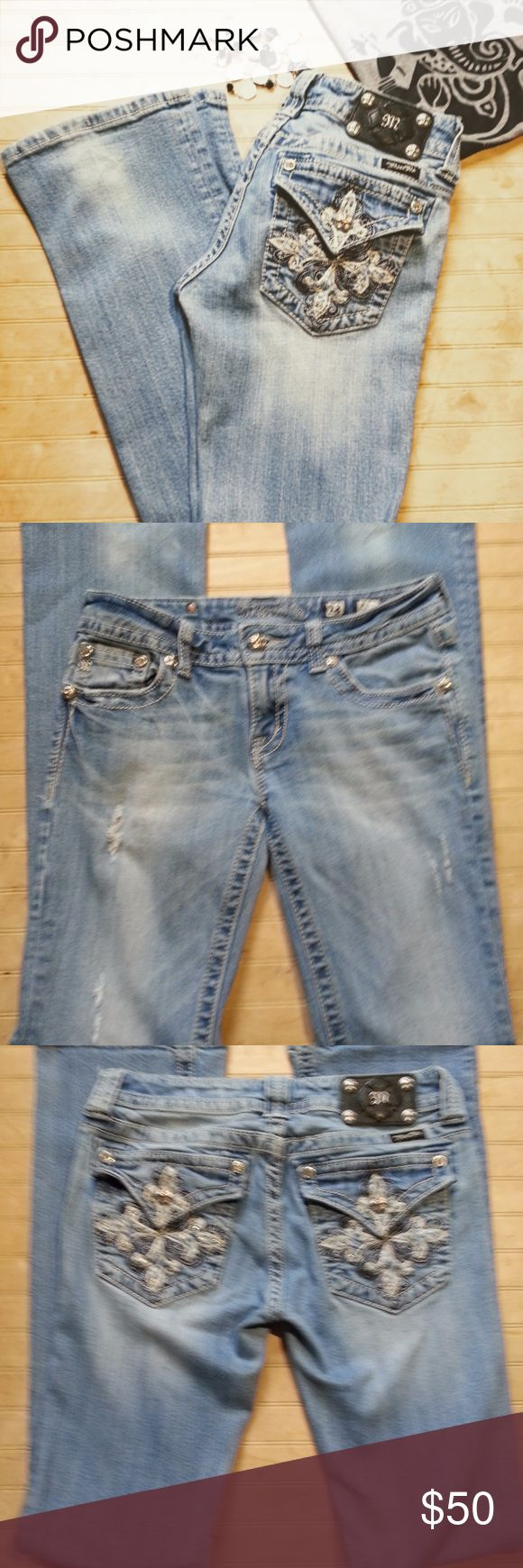 """Miss Me Bootcut Jeans!  Make an offer! Flap pocket with white and blue Fleur-de-lis cross design, distressed thigh, medium wash, white contrast stitching, rhinestone and large crystal rivets, and classic black logo patch.   These are in excellent condition with no staining or damage besides factory distressing.  Waist 14.5"""" Rise 7.5"""" Inseam 32"""" Leg 8"""" Miss Me Jeans Boot Cut"""