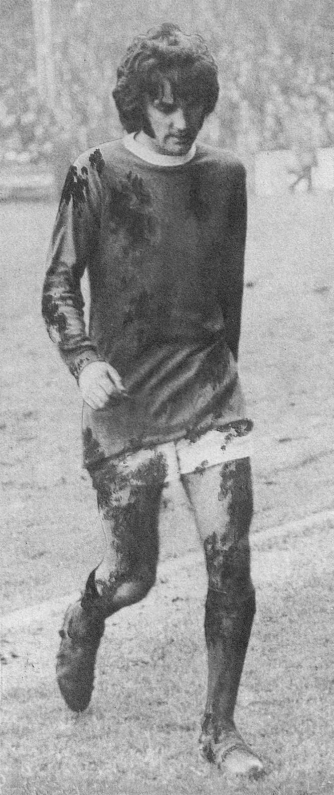Circa 1969/70. Manchester United winger George Best finding football no longer fun as he trudges off following heavy rain.