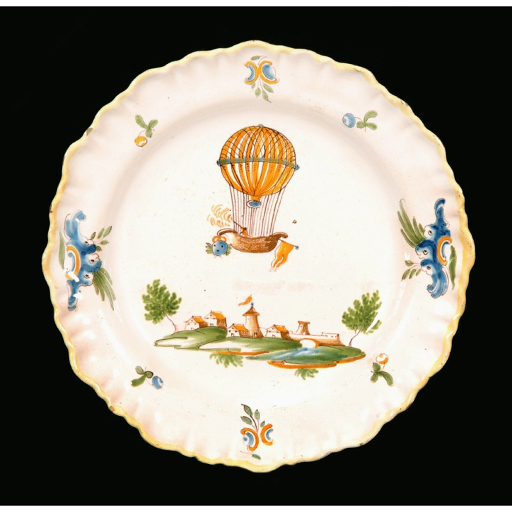 """French Faience Plate. Decorated with a Frilled Rim, an Ascension Balloon above a Fortified Castle, with Sprigs of Fruit and Rococo Scrolls. France. Circa 1780. 9-3/4"""" (24.77cm)."""