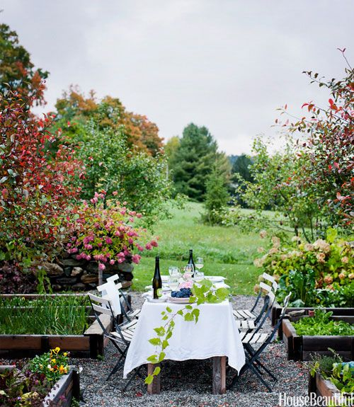 "Designers Deirdre and Caleb Barber often entertain in their cozy Vermont cottage's kitchen garden, between raised vegetable and flower beds Barber made out of red cedar from a garage they tore down. ""We love the idea of the weekend country-house party in the European style, where everyone sits around the farmhouse table having long, leisurely meals, eating food made from the garden, and drinking interesting and honest wine."" Ditte Isager  - HouseBeautiful.com"