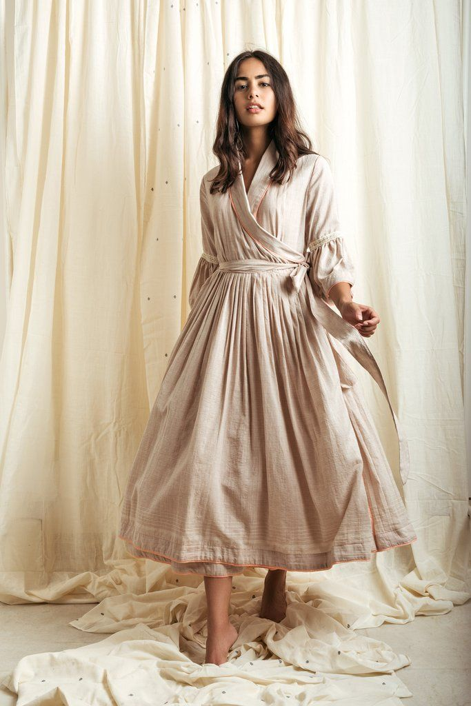 this taupe fine pin striped wrap dress is a perfectam to pm wardrobesolution.This piece is a crafted pure hand-woven khadi muslin stripes,withcontrast piping details STYLE TIP:wrap it as a dress, or layer is an over cape DETAILS -Khadi Muslin -Handwoven -A line flared silhouette with contrast peach piping details-pleats at the waist -Straight cut sleeves withflared puff cuff details -shawl collar-comes with a fabric belt-the garementis lined-side button for closer -Dry clean only…