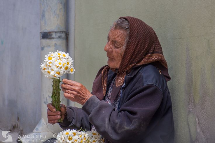 Old woman selling flowers. Sighisoara, Romania.