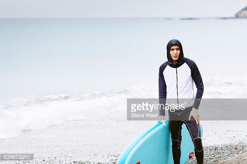 Young athletic man standing on the beach holding a Stand Up Paddleboard