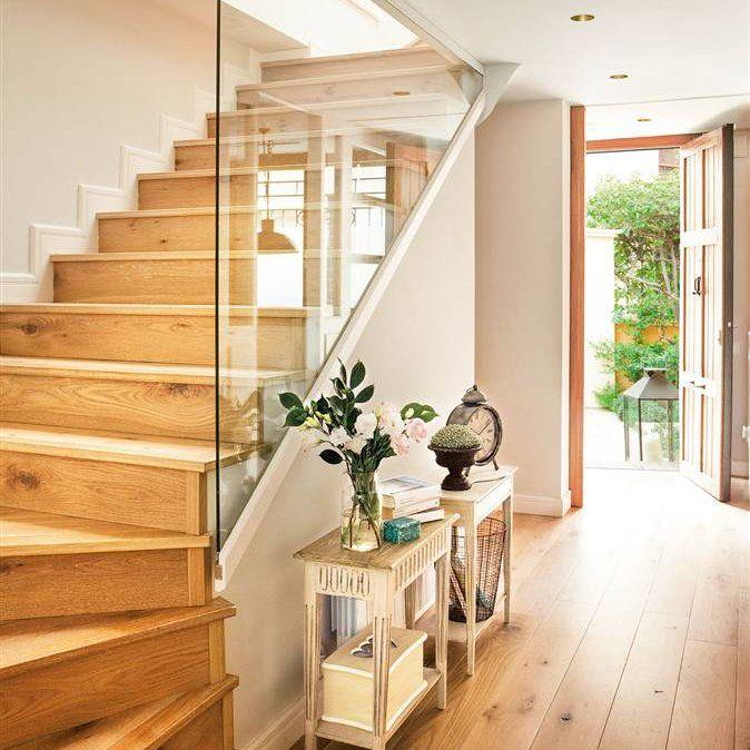 recibidor con suelo de parquet y escaleras en madera con separacin de cristal y exentas de