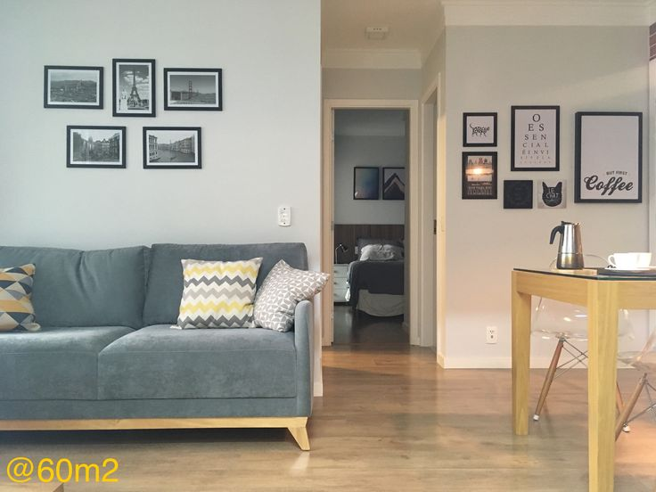 Sala pequena (apartamento 60m2), paredes cinza, moldura de gesso, paredes de quadros, fotografias nas paredes, sofá cinza com pés de madeira, piso laminado carvalho, rodapé branco, mesa de madeira e vidro